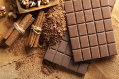 Four chocolate bars, cinnamon sticks, cocoa and mixed nuts Stock Photo