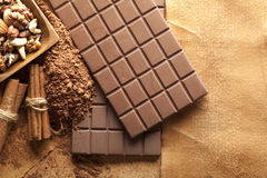 Four chocolate bars, cinnamon sticks, cocoa and mixed nuts Stock Image