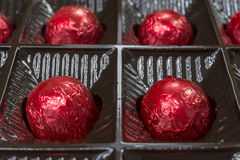 Four chocolate candy in red foil Royalty Free Stock Photo