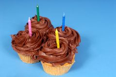 Four chocolate frosted cupcakes with candles with a blue backgro Stock Photography