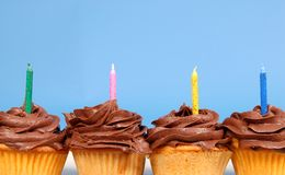 Four chocolate frosted cupcakes in a row with candles Royalty Free Stock Photography