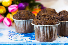 Four chocolate muffins on a background of tulips. Chocolate muffins on the board written under gzhel Royalty Free Stock Photography
