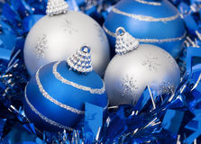 Four Christmas balls on a blue ribbon. Two balls are blue and the other two are silver stock photos