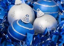 Four Christmas balls on a blue ribbon Stock Photos