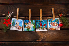 Four christmas cards hanging on rope against wooden background Stock Image