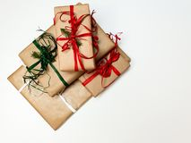 Four Christmas gift boxes crafted and red and green ribbons on a white background stock image