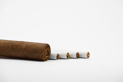 Four cigarettes and cigar. On white Stock Image