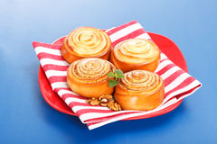 Four cinnamon rolls on red plate Stock Image