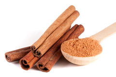 Four cinnamon sticks and powder with spoon isolated on white background Stock Image