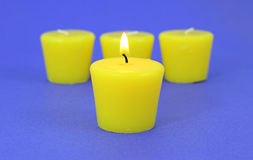 Four citronella candles with one lit Stock Photo