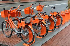 Four City Orange `Rent-a-Bikes` in Portland, Oregon. These are four of the many orange city `rent-a-bikes available for use throughout Portland, Oregon`s Stock Photos