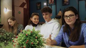 Four classmates sat at the tables and worked on something, and then they noticed that they are photographed, they began. Classmates sat at the tables and worked stock video