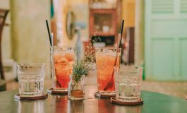 Four Clear Glass Drinking Cups Filled With Orange and Clear Liquids on Black Surface stock photos