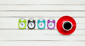 Four clocks and cup Royalty Free Stock Images