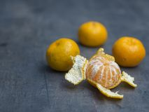 Four close up tangerine mandarin orange one peeled on defocused Royalty Free Stock Image
