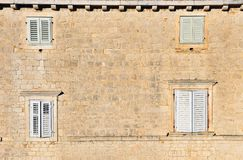 Four closed windows in the old stone house. Four closed windows in the old stone mediterranean house Royalty Free Stock Photography
