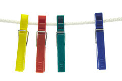 Four clothes-spins. Four colorful clothes-pegs/clothespins hanging on string (isolated on white Stock Photography