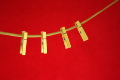 Four clothespins on rope. Red background Stock Photo