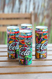 Four Coca Cola cans. Woodstock edition on a wooden table Royalty Free Stock Photography