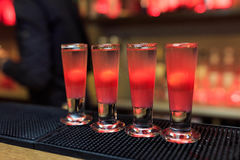 Four cocktails in red standing in a row. On rack Stock Photo