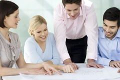 Four colleagues discussing architects plans Stock Photos