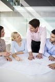 Four colleagues discussing architects plans Stock Images
