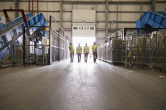 Four colleagues leaving a warehouse approach the exit royalty free stock images