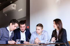 Four colleagues of man and woman gather for meeting at office of. Three managers who are held discuss agenda and are waiting for start of business meeting with stock photography