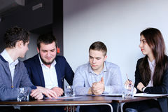 Four Colleagues Of Man And Woman Gather For Meeting At Office Of Stock Image
