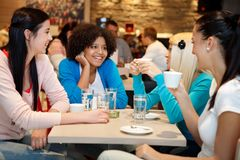 Four college chatting in a coffee shop. Four young women college chatting in a coffee shop Royalty Free Stock Image