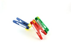 Four color clothes-pegs. Abstract shape from four color clothes-pegs over white Royalty Free Stock Images
