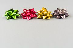 Four color festive bows over grey background Royalty Free Stock Photos