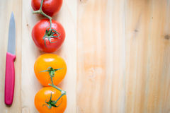 Four color tomatoes in line on top of a wood table with knife. Royalty Free Stock Photos