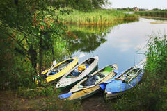 Four colored boats on the shore of small river stock images