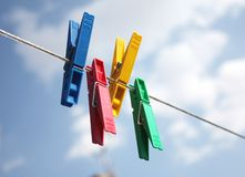 Four colored clothes pegs. Hanging on clothesline royalty free stock photo
