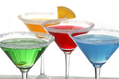 Four colored cocktails 2. A close up view of martini glass with different colored cocktails and a piece of orange Royalty Free Stock Photography