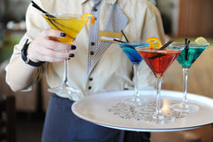 Four colored cocktails on a tray in the hands of the waiter. Yellow, blue, green, red. Waiter raises a yellow. Waiter delivers four colored cocktails on the tray stock images