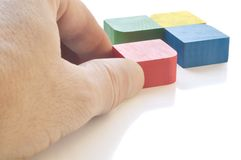 Four colored cubes and hand. Against white background Royalty Free Stock Photos