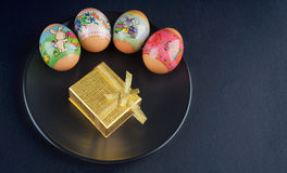 Four colored Easter eggs and giftbox Stock Photography