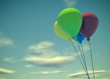 Four colorful balloons on summer sky. Four colorful balloons on a blue sky, vintage color toned 3d rendering with space for text Royalty Free Stock Image
