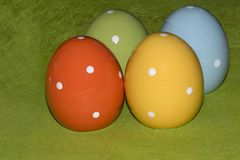 Colorful ceramic easter eggs in front of a green background. Four colorful ceramic easter eggs in front of a green background with place for Easter greetings royalty free stock photography