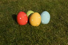 Colorful ceramic easter eggs which are standing in the grass. Four colorful ceramic easter eggs which are standing in the grass. Place for Easter greetings royalty free stock photos