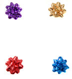 Four colorful Christmas bows in the four corners of an isolated. Four bright colorful Christmas bows in the four corners of an isolated white background forming Royalty Free Stock Photography