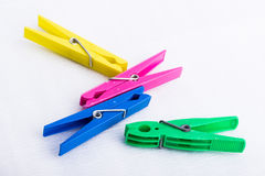 Four colorful clothespins on a white surface Royalty Free Stock Images