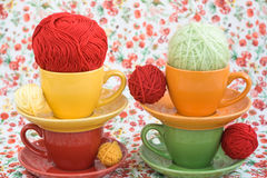 Four colorful cups and balls of yarn on a background Royalty Free Stock Photography