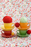 Four colorful cups and balls of yarn on a background Stock Image