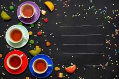 Four colorful cups of tea, marmalade and biscuits on a black background. Free space for text. Royalty Free Stock Photo