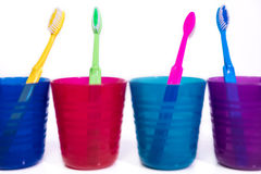 Four colorful cups with toothbrushes, white background Royalty Free Stock Photos