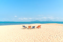 Four colorful deckchairs on the beach Stock Image