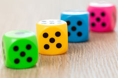 Four colorful dice on the wooden surface Royalty Free Stock Photography